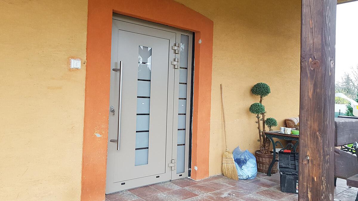 Hliníkové vchodové dvere do rodinného domu vo farbe RAL 1019 s pieskovaným sklom a bočným svetlíkom
